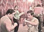 Breno dá dicas de arte marcial para Ariel, enquanto Rita faz pose no palco.